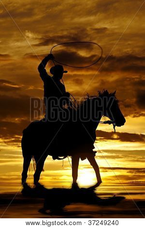 A cowboy is sitting on his horse in the sunset and swinging a rope standing in water. poster