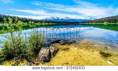 Patricia Lake With Reflections Of The Snow Capped Peaks Of The Rocky Mountains In Jasper National Pa