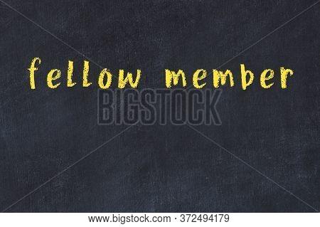 Chalk Handwritten Inscription Fellow Member On Black Desk