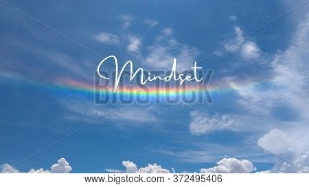 Inspirational Quote Written On A Cloudy Sky With A Rainbow. Message With The Phrase Mindset. Message