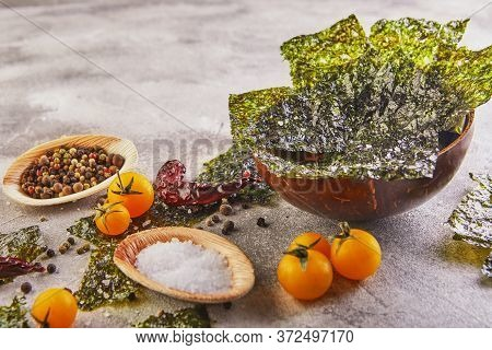 Crispy Nori Seaweed With Cherry Tomatoes And In A Wooden Bowl On Gray Concrete. Japanese Food Nori.