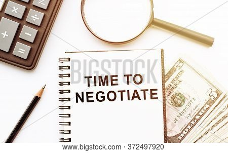 Notebook With Text Time To Negotiate On White Table With Calculator, Magnifier, Pencil And Dollars.