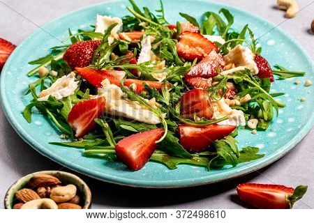 Fresh Salad With Arugula, Strawberries And Cheese Brie, Camembert. Healthy Organic Diet Food Concept
