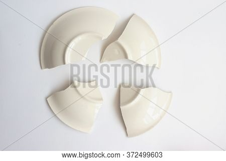 A Broken White Ceramic Plate On The White Floor. Fragments Of A Plate On A White Background.tablewar