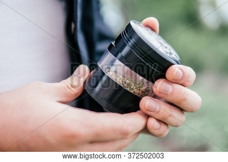 The Pot Leaves On Buds. Cannabis Nature Bud. Smoking Pipe In Hand. Marijuana Weed Bud And Grinder.