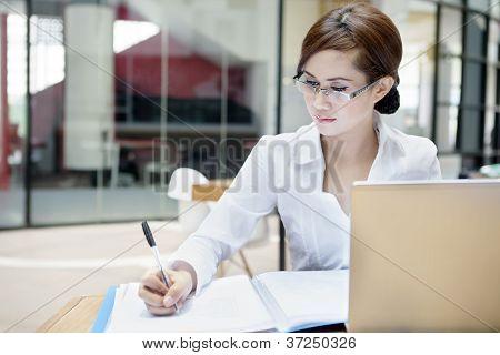 Empresaria escribe en un documento