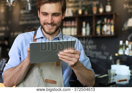 Young Male Owner Using Digital Tablet While Standing In Cafe.