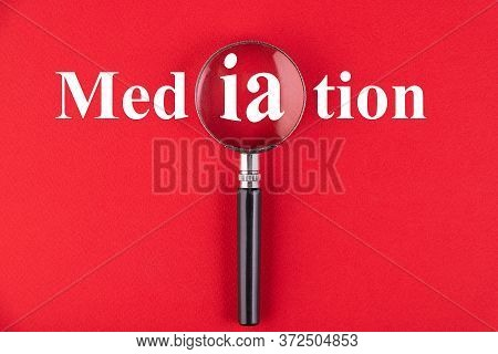 Mediation Text Written Through A Magnifying Glass On A Red Background. Business Education Concept.