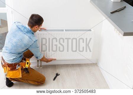 Man Is Repairing Radiator Battery In The Room. Maintenance Repair Works Renovation In The Flat. Heat