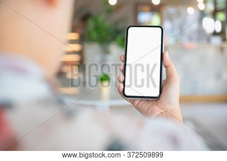 Back View Close Up Of A Person Using Smartphone Mockup Blank Screen In Home Interior. Mock Up White