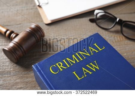 Gavel And Book On Wooden Table. Criminal Law Concept