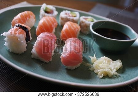 Japanese Sushi Food. Sushi Set On Green Plate Served With Ginger And Soy Sauce. Sushi Rolls, Salmon