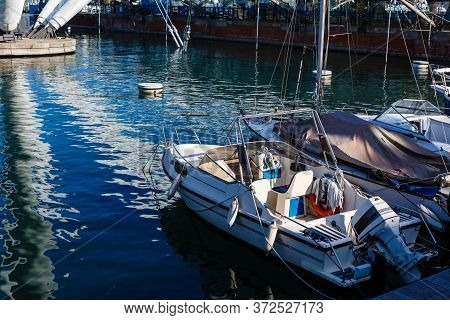 Yacht In Port Near The Pier. Speed Boat Mooring. Boat Parking Boating Yachting Equipment.