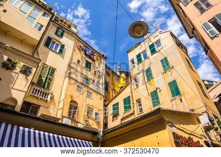 Genoa, Italy - August 20, 2019: Looking Upward A Narrow Street With Traditional Yellow Houses In Gen