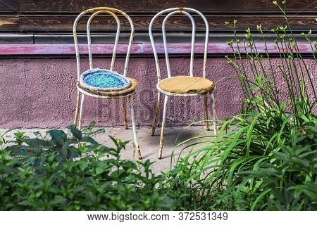 Two Old Metal Chairs Stand Against The Wall Of A Residential Building Close