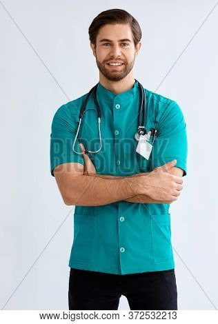 Studio Portrait Of A Focused Looking Male Nurse Against A White Background