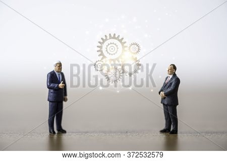 Two Businessmen Standing And Discussion With Cog Gears. Brainstorming Idea Concept.