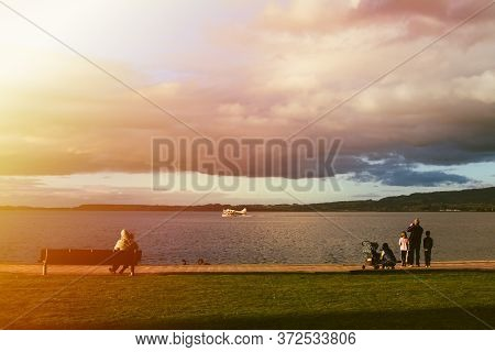 Young Families Watching A Seaplane Speeding Up To Take Off From The Lake Rotorua At Sunset