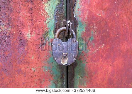 Closed On An Old Padlock Metal Door Leaf Close Up