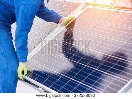 Technician Wearing A Safety Suite And Working On Solar Power Panels