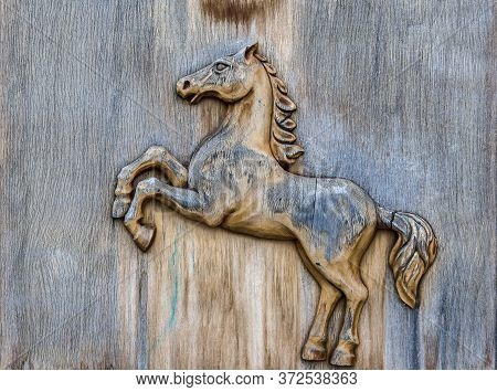 Image Of A Horse Carved On A Wooden Board Surface Close Up