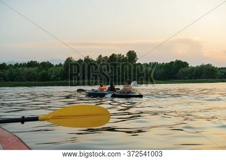 Family Kayaking On The River In The Summer At Sunset.