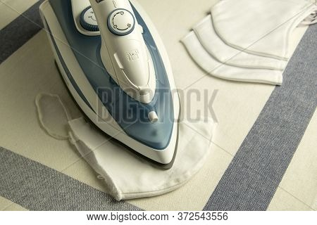 Iron Is An Electrical Appliance For Homework. Ironing Of Textile Maske. Ironing  On The Table.top Vi