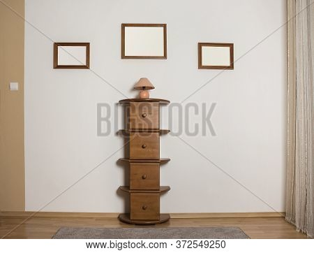 Empty Wooden Frames On A Wall With A Commode