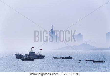 Various Fishing Boats Moored Offshore In Fushan Bay With A Hazy View Of The City Of Qingdao China, S