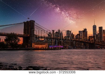 Beautiful View Of The Brooklyn Bridge With Starry Sky Over It. Milky Way Galaxy Seen Over Brooklyn B