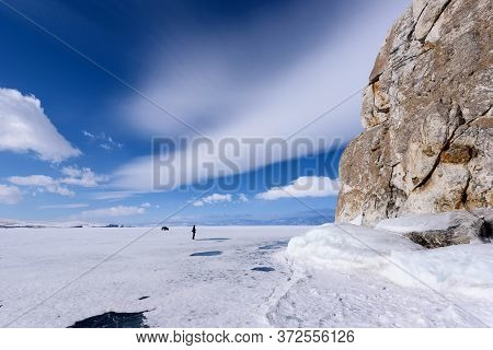 Silhouette Of Man Stands Near Cape Burhan On Shamanka Rock In Olkhon Island Covered With Icicles In