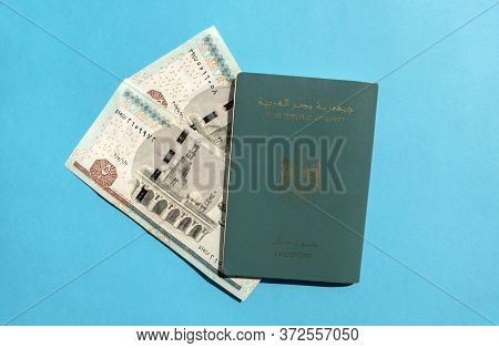 Arab Republic Of Egypt Passport With Egyptian Currency Pound Isolated On Blue Background. Egyptian P