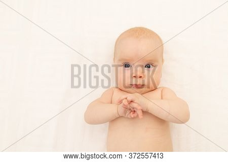 Cute Baby Girl In A White Bodysuit On A White Isolated Background Looking At The Camera, Baby 3 Mont