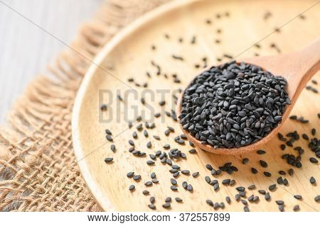Black Sesame Seeds On Wood Spoon. The Benefits Of Black Sesame Help To Strengthen Hair Roots And Hel