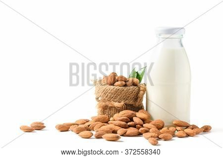 Bottle Of Milk And Almonds Nuts With Leaf Isolated On White Background, Almonds Are Very Popular Nut