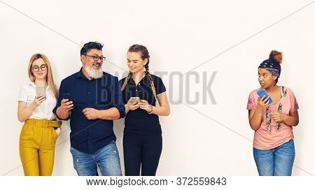 Young African American Girl Playing Alone On Mobile Phone While Group Of Mixed People Having Fun Ign