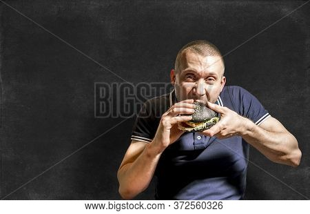 A Hungry Man Enjoys Eating A Black Burger On The Background Of A Chalkboard.