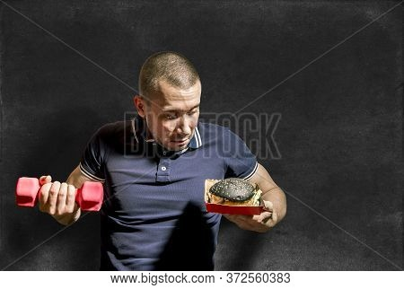 A Man Holds A Black Burger In One Hand And A Dumbbell In The Other Against The Background Of A Chalk