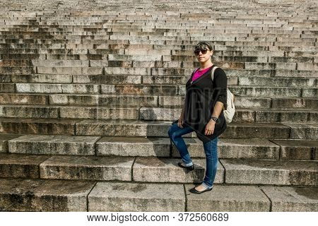 Girl Tourist Posing Standing On A Granite Staircase.
