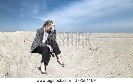 Woman In Office Clothes Is Sitting On A Dune In The Desert, Holding Her Head In Her Hands. The Conce