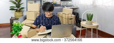 Asian Man Working Sell Online Writing Address On Package Of Orders With Cardboard Box To Send Out To