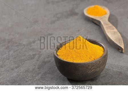Turmeric Powder In The Wooden Bowl - Curcuma Longa