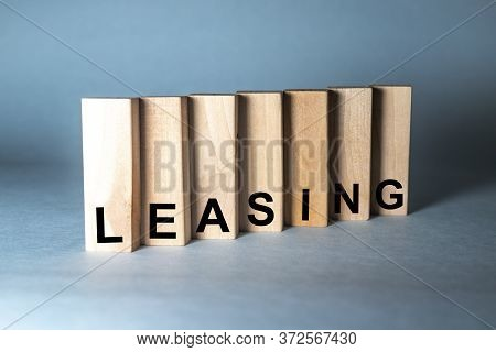 Leasing Word Written In Wooden Blocks On Blue Grey Background
