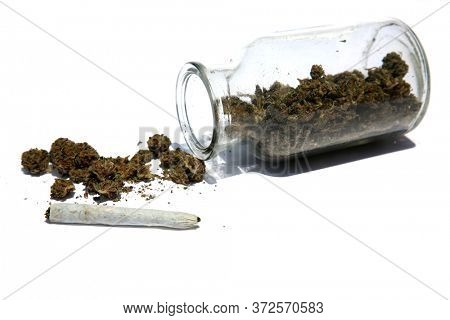 Marijuana in a clear Stash Jar with a Rolled Joint. Cannabis. Pot. Medical Marijuana. Recreational Marijuana. Marijuana and Cannabis stores well in a closed Stash Jar. Isolated on white. Room for text