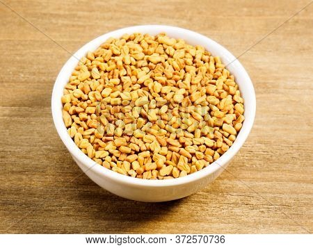 Spice Fenugreek In White Bowl On Brown Wood Background With Copy Space. Healthy Eating, Ayurveda, Na