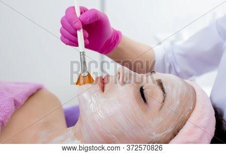 Face Peeling Mask, Spa Beauty Treatment, Skincare. Woman Getting Facial Care By Beautician At Spa Sa