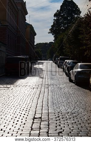 Paving Stones In Backlight. A Paved Road Stretching Into The Distance. Historic Center.