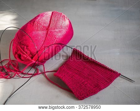 Homework, Knitting With Satin Stitch Of Raspberry-colored Hexagons And A Skein Of Yarn