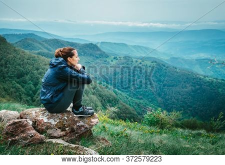 Sad Depressed Woman Sitting On Rock In Raincoat. Rear View Of Depressed Woman. Woman In Depression.