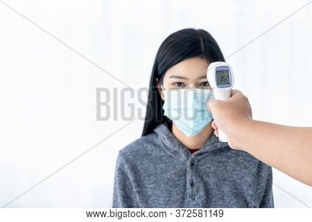 Blurred Soft Images Of People Using Infrared Thermometer For Measuring The Temperature Of Women Wear